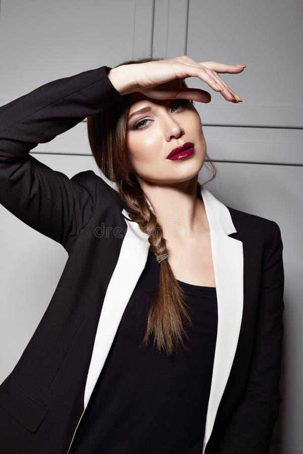Den härliga unga sexiga brunettkvinnan som bär en stilfull design för kort klänning och ett trendigt omslag med den vita gränsen, arkivbild