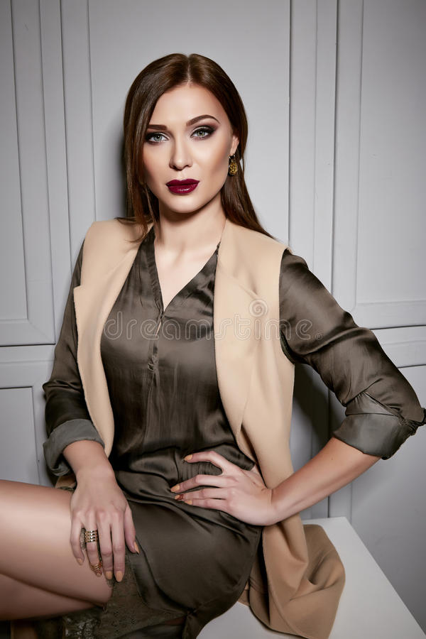 Den härliga unga sexiga brunettkvinnan som bär en stilfull design för kort siden- klänning och ett trendigt omslag, beigea häl, s royaltyfri bild