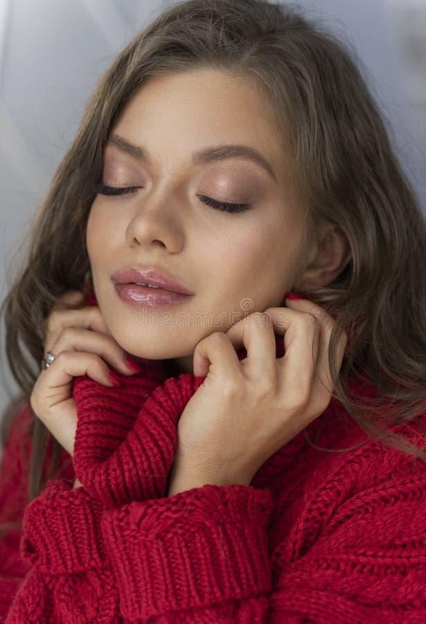 Den härliga unga sexiga eleganta flickan tycker om mjukheten och värmen av en röd ulltröja Reklamfilm- och advertizingdesign clos arkivbild