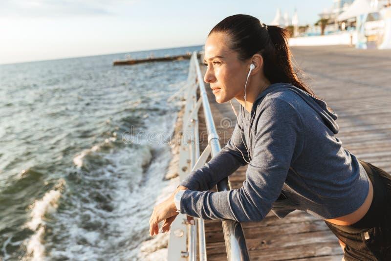 Den härliga unga sportkonditionkvinnan har att vila på lyssnande musiken för stranden den utomhus med hörlurar royaltyfri foto