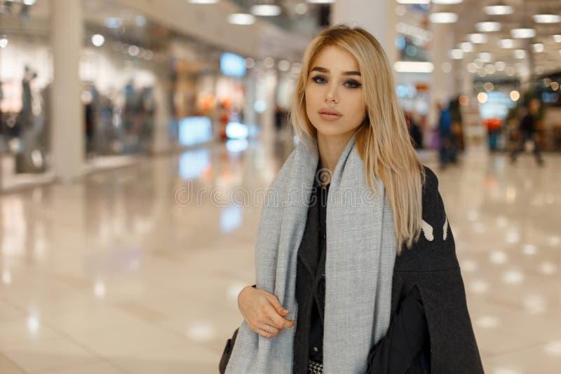 Den härliga unga trendiga blonda kvinnan med gråa ögon i stilfull elegant höstkläder går till och med gallerian arkivbild