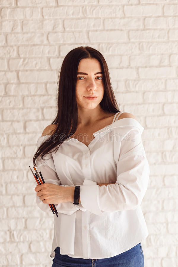 Den härliga unga uppsättningen för kosmetologkvinnainnehavet av sminket borstar arkivfoto