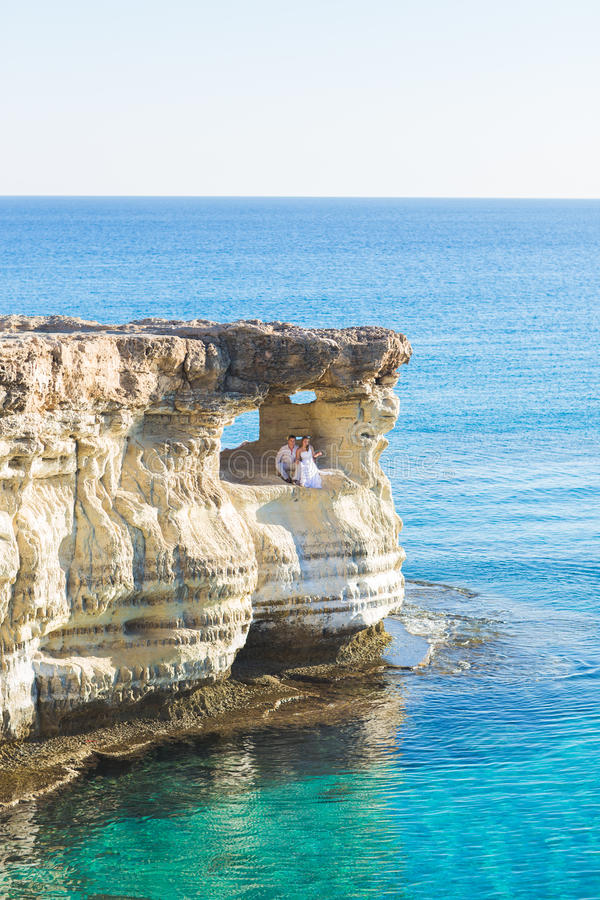 Den härliga ursnygga bruden och den stilfulla brudgummen vaggar på, på bakgrunden av ett hav, bröllopceremoni på Cypern arkivbilder
