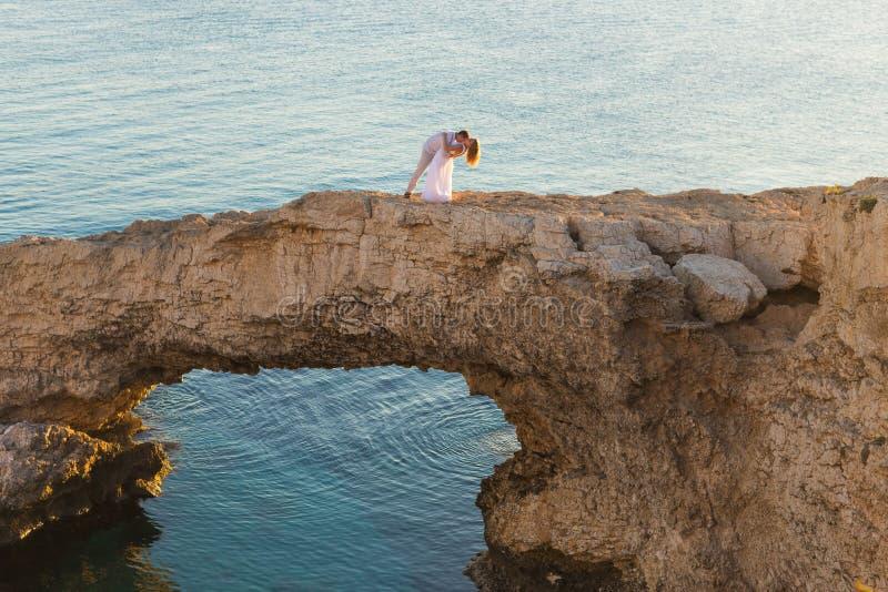 Den härliga ursnygga bruden och den stilfulla brudgummen vaggar på, på bakgrunden av ett hav, bröllopceremoni på Cypern royaltyfria bilder