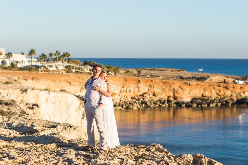 Den härliga ursnygga bruden och den stilfulla brudgummen vaggar på, på bakgrunden av ett hav, bröllopceremoni på Cypern royaltyfri bild