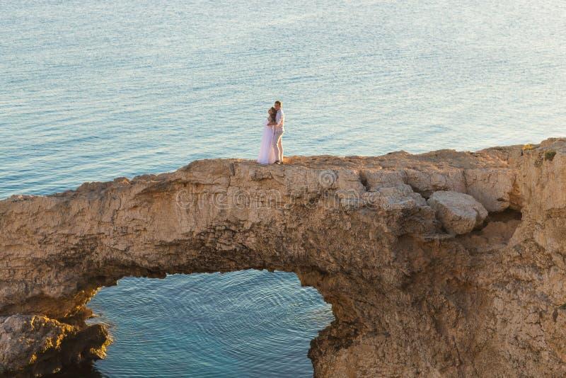 Den härliga ursnygga bruden och den stilfulla brudgummen vaggar på, på bakgrunden av ett hav, bröllopceremoni på Cypern arkivfoton