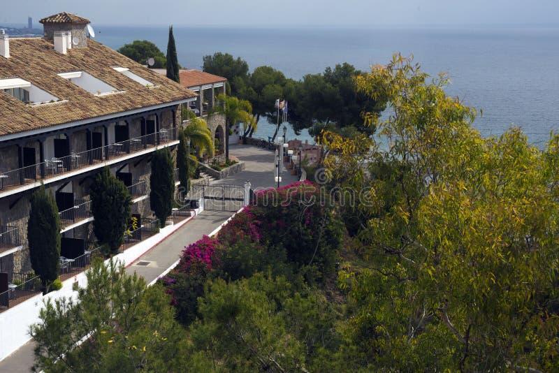 Den härliga villan mot bakgrunden av det medelhavs- fördjupas i vårblommor royaltyfria bilder