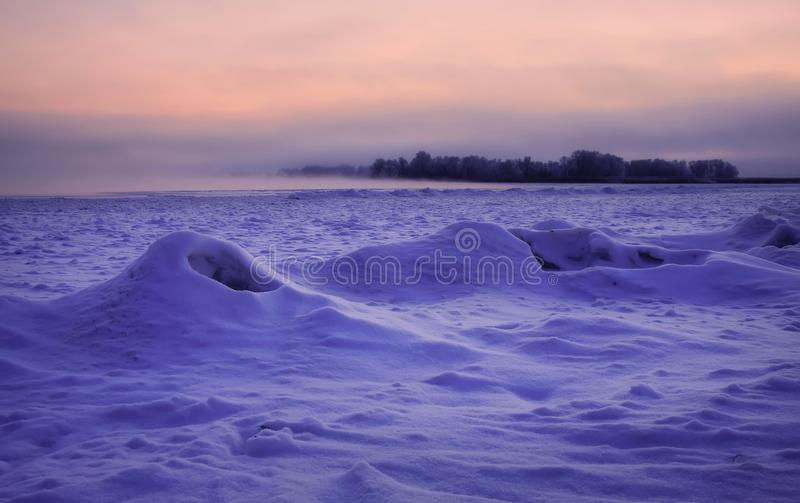 Den härliga vintern landscape Djupfryst flod som täckas med snö royaltyfria foton