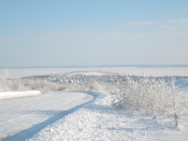 Den härliga vintern landscape Vägen täckas med snö och byn i avståndet med snö-täckte hus arkivbild
