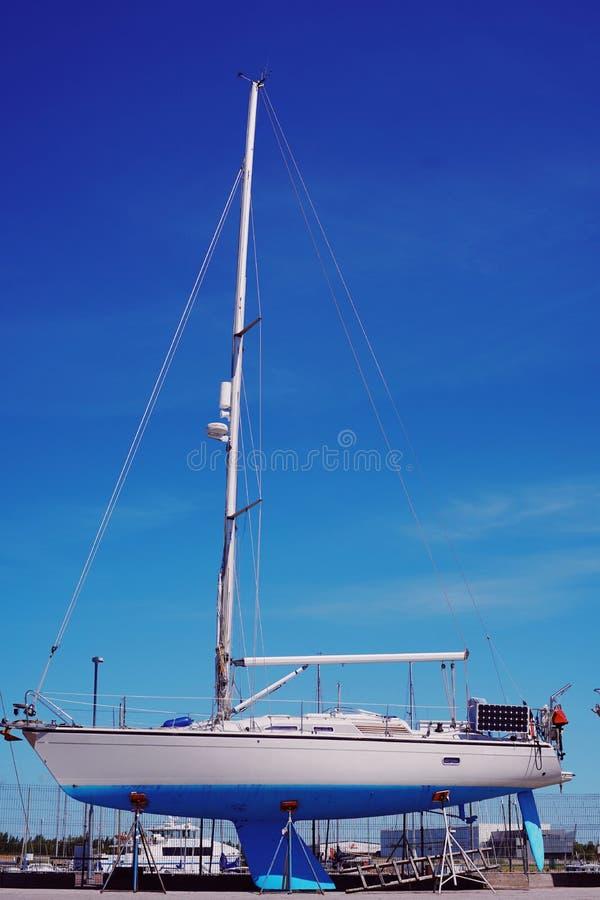 Den härliga vita blåa segelbåten står på skeppsdockan och väntar på lanseringen Sommar arkivbilder