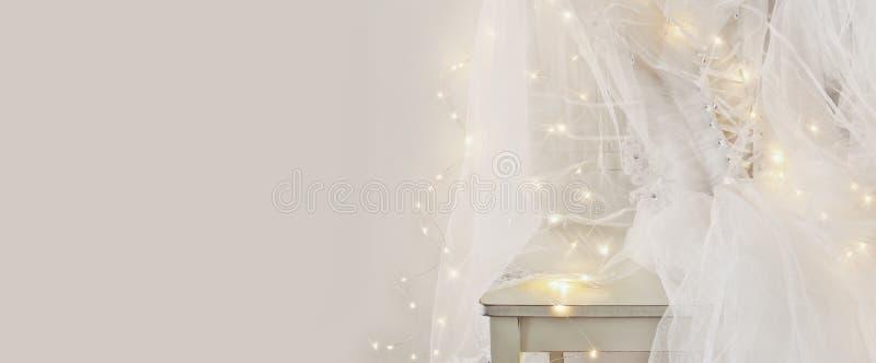 Den härliga vita bröllopsklänningen och skyler på stol med guld- girlandljus fotografering för bildbyråer