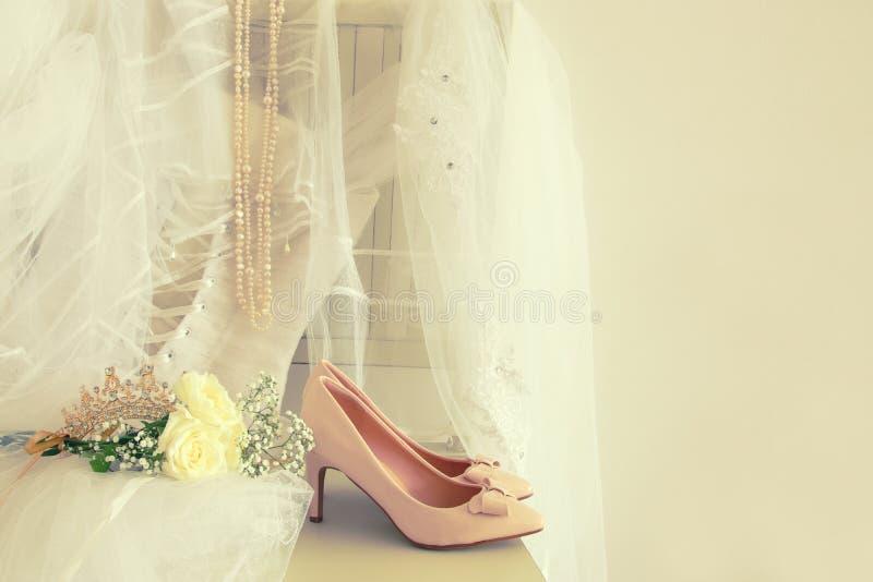 Den härliga vita bröllopsklänningen, skor, guld- diamanttiara och skyler på stol royaltyfri bild