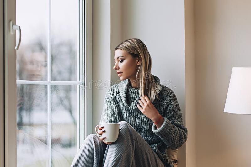 Den härliga vita stilfulla kvinnan i hemtrevlig scandinavian interrior sitter hemma nära det stora fönstret, ståenden av det härl arkivbilder