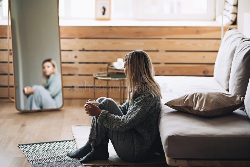Den härliga vita stilfulla kvinnan i hemtrevlig scandinavian interrior sitter hemma nära det stora fönstret, ståenden av det härl royaltyfria bilder