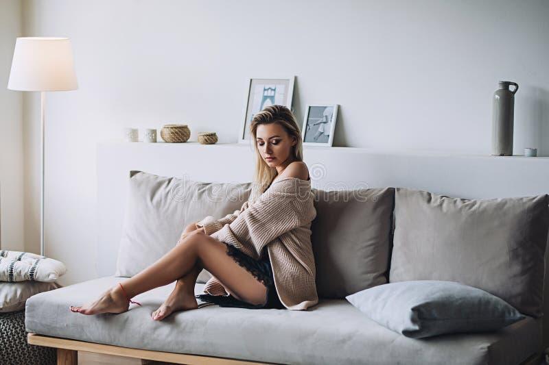 Den härliga vita stilfulla kvinnan med länge nacked ben i hemtrevlig scandinavian interrior sitter hemma, ståenden av royaltyfri foto