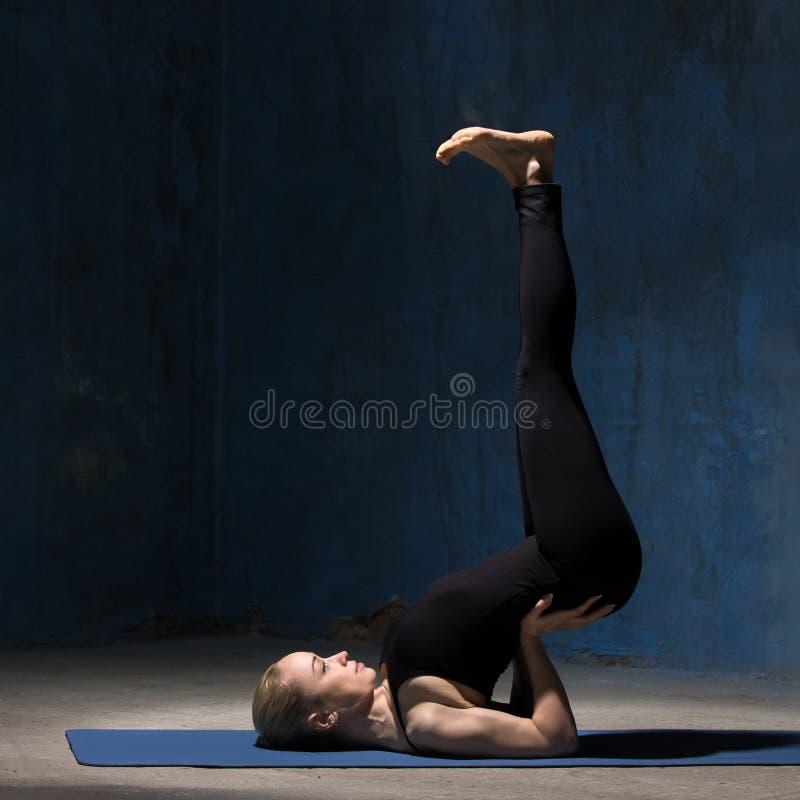 Den härliga yogakvinnan som gör uppochnervänd skyddsremsayoga, poserar arkivfoto