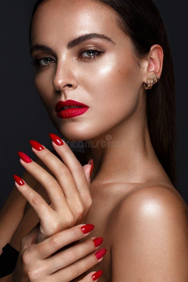 Den härligt flickan med ett klassiskt smink och rött spikar Manikyrdesign Härlig le flicka royaltyfri foto