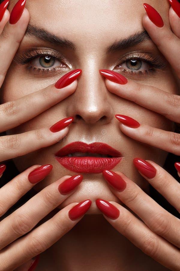 Den härligt flickan med ett klassiskt smink och rött spikar Manikyrdesign Härlig le flicka royaltyfri fotografi