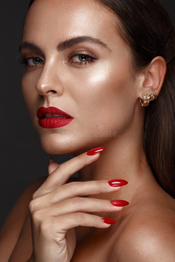 Den härligt flickan med ett klassiskt smink och rött spikar Manikyrdesign Härlig le flicka royaltyfria foton