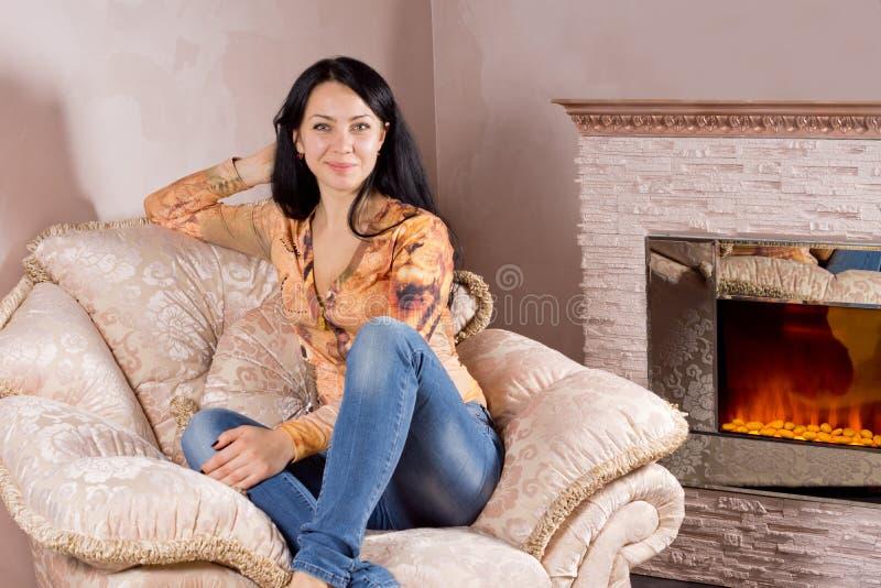 Härlig kvinna i en bekväm fåtölj royaltyfri foto