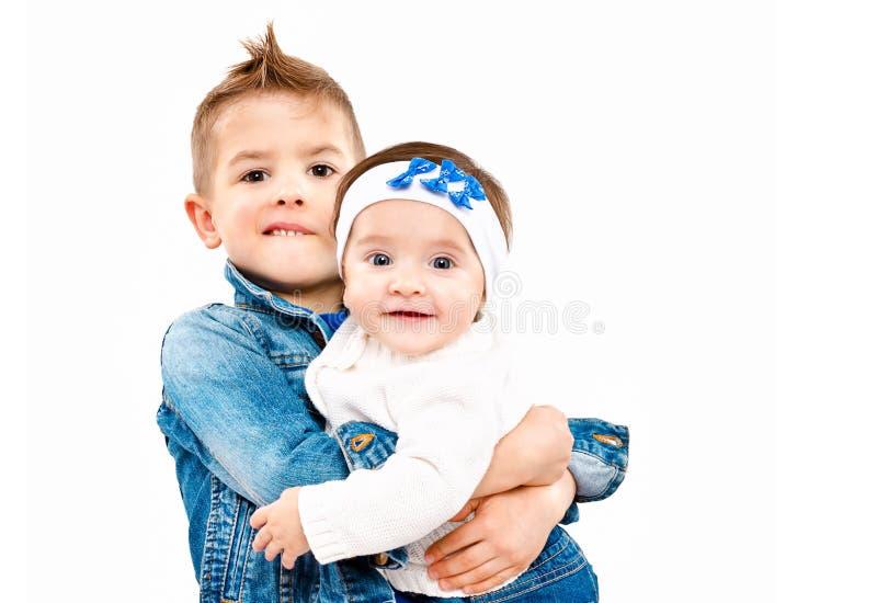 Den hållande brodern räcker på hans gulliga lilla syster royaltyfri fotografi