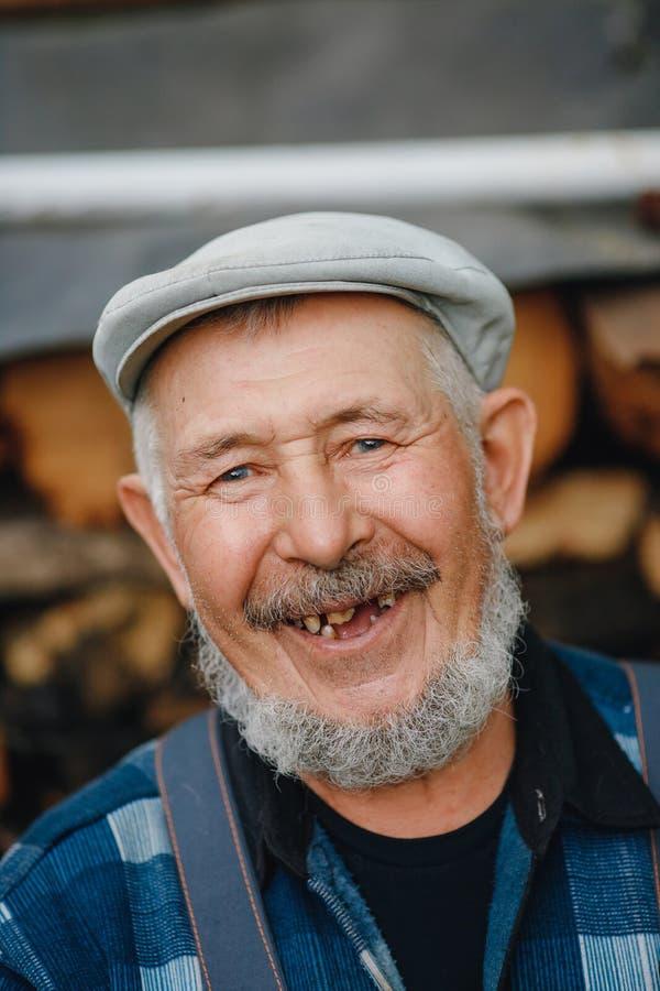 Den höga äldre mannen med ingen tänder och karies ser leenden royaltyfria foton