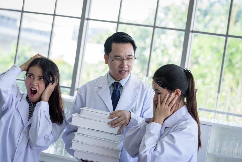 Den höga asiatiska forskaren har att tilldela nytt jobb till studenter i laboratorium royaltyfria bilder