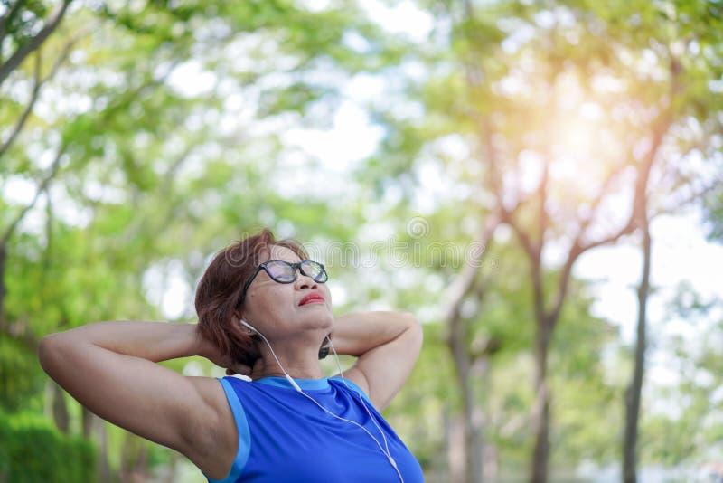 Den höga asiatiska kvinnan kopplade av att lyssna till musik i parkerar, Exerc royaltyfri foto