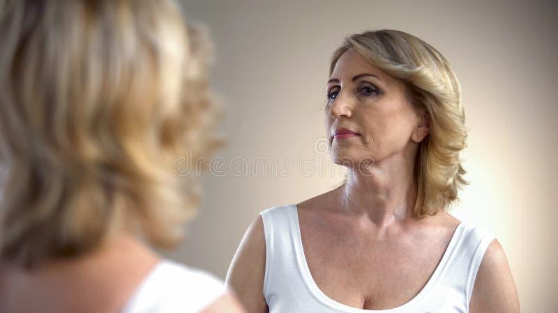 Den höga damen med utgör och den trevliga frisyren som ser i spegeln, förberedelse fotografering för bildbyråer