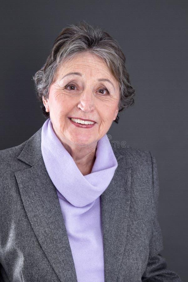 Den höga damen tillfredsställde - äldre kvinna som isolerades på svart bakgrund royaltyfria foton