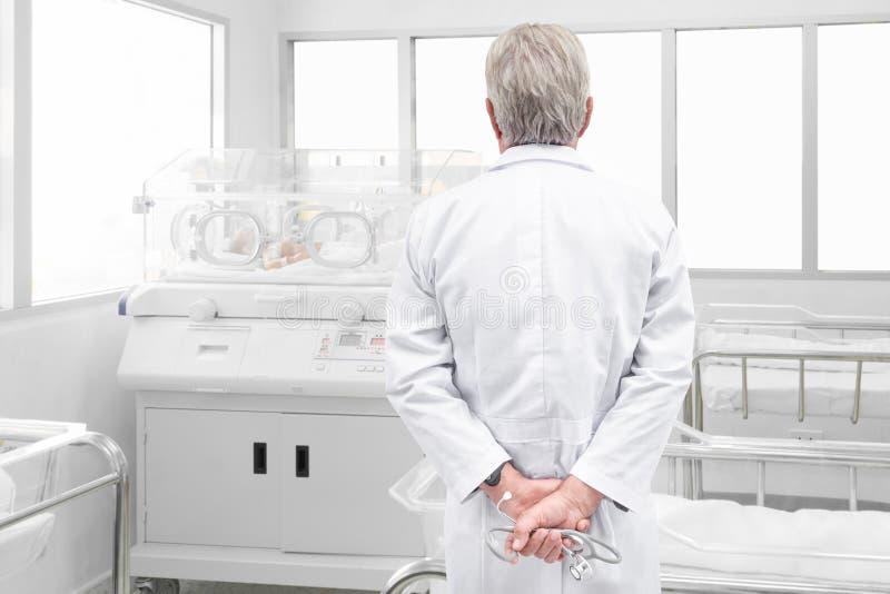 Den höga doktorn med stetoskopet som ser nyfödd, behandla som ett barn dolt I arkivfoto