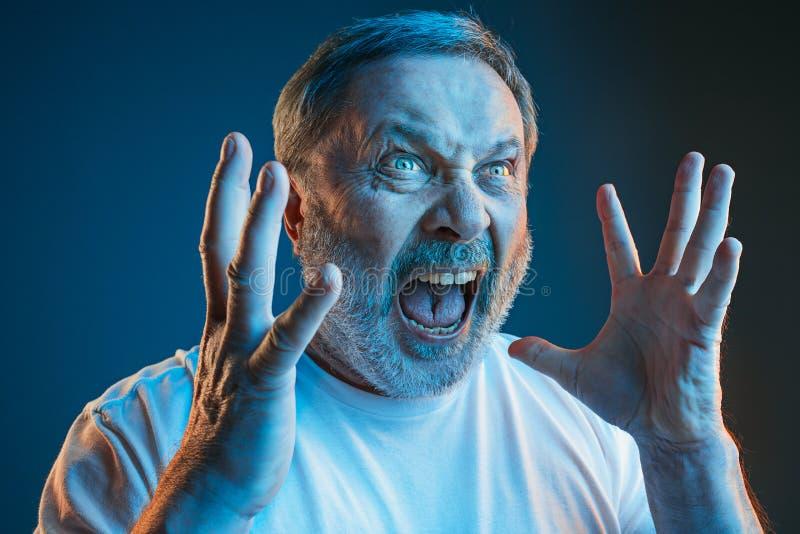 Den höga emotionella ilskna mannen som skriker på blå studiobakgrund arkivbild