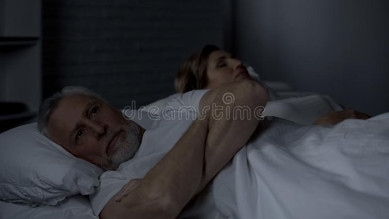 Den höga förargade mannen som ligger i säng som tillbaka vänds till kvinnan, missförstånd, grälar arkivbilder