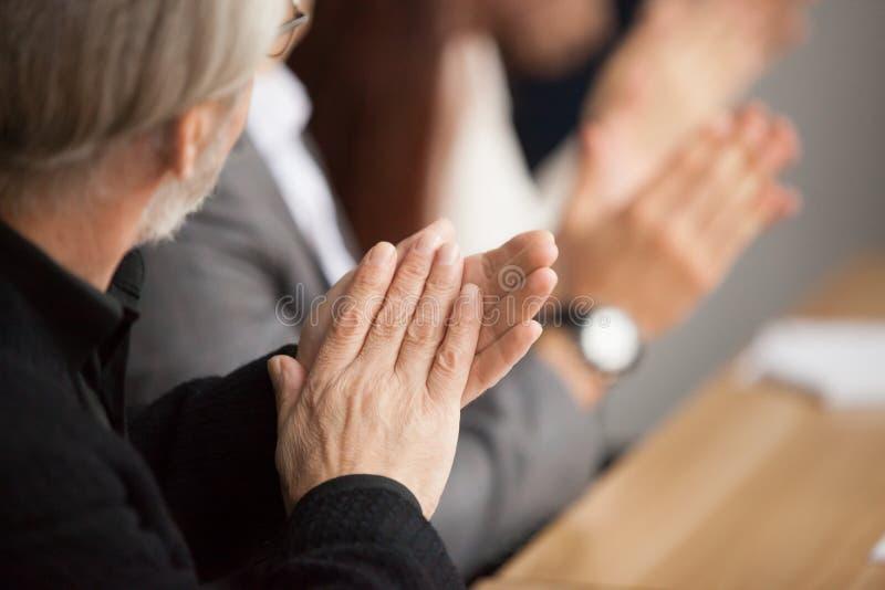 Den höga gråhåriga affärsmannen som applåderar händer som deltar i, conferen royaltyfria bilder