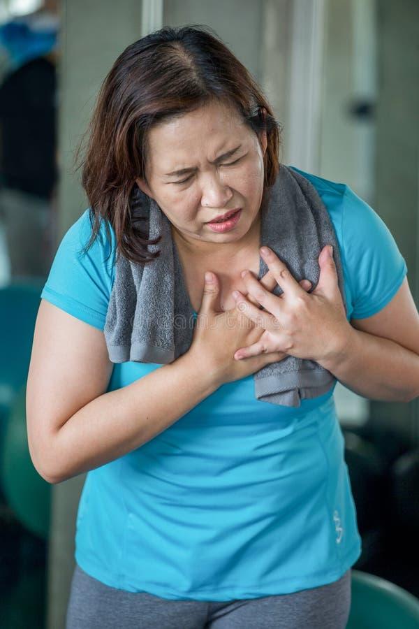 Den höga konditionkvinnan som lider från bröstkorg, smärtar, medan öva i idrottshall åldras damhjärtinfarkt r mogen sport royaltyfria foton