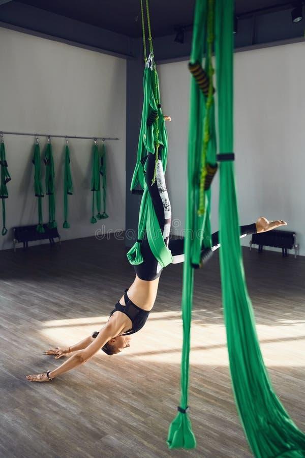 Den höga kvinnan öva antigravity yoga för olik inversion arkivbilder