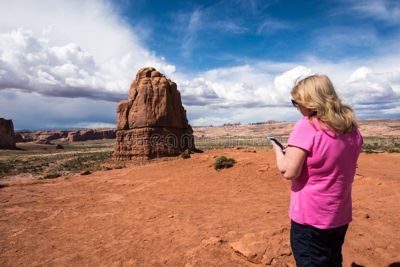 Den höga kvinnan använder hennes smarta telefon för att smsa, medan att besöka välva sig nationalparken i utah arkivbilder