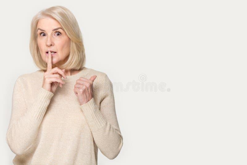 Den höga kvinnan gör hyssjar tecknet som åt sidan pekar fingret på copyspace royaltyfri foto