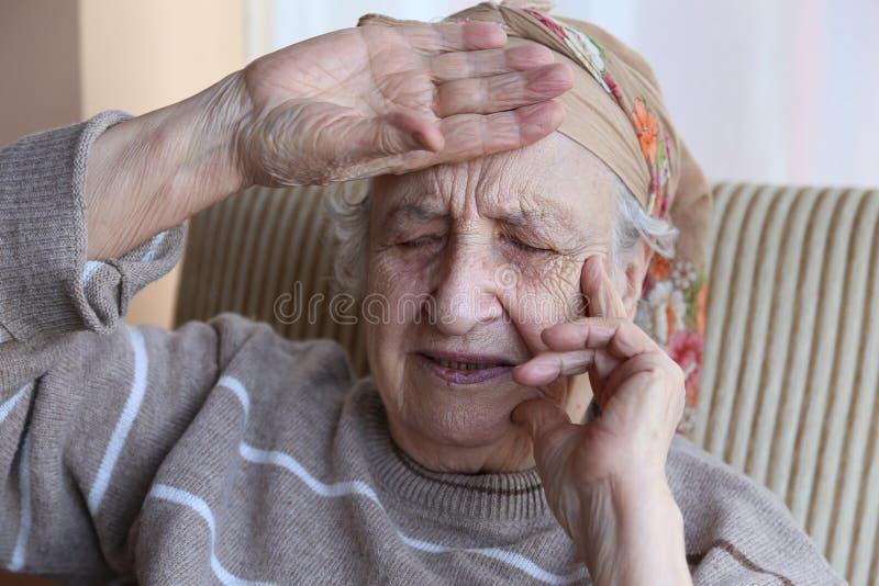 Den höga kvinnan har huvudvärk arkivfoton