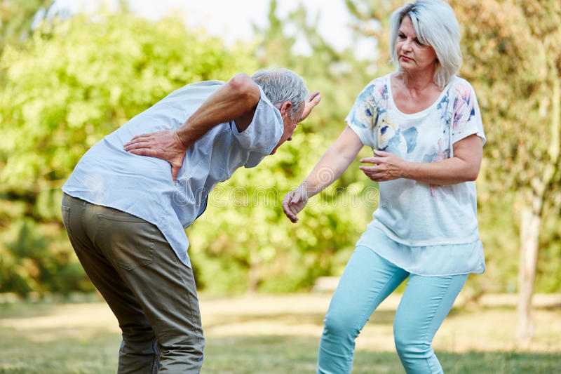 Den höga kvinnan hjälper mannen som har ryggskott att smärta royaltyfri fotografi