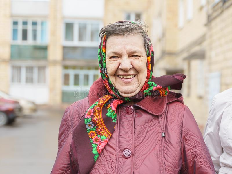 Den höga kvinnan i en sjalett ler royaltyfria foton