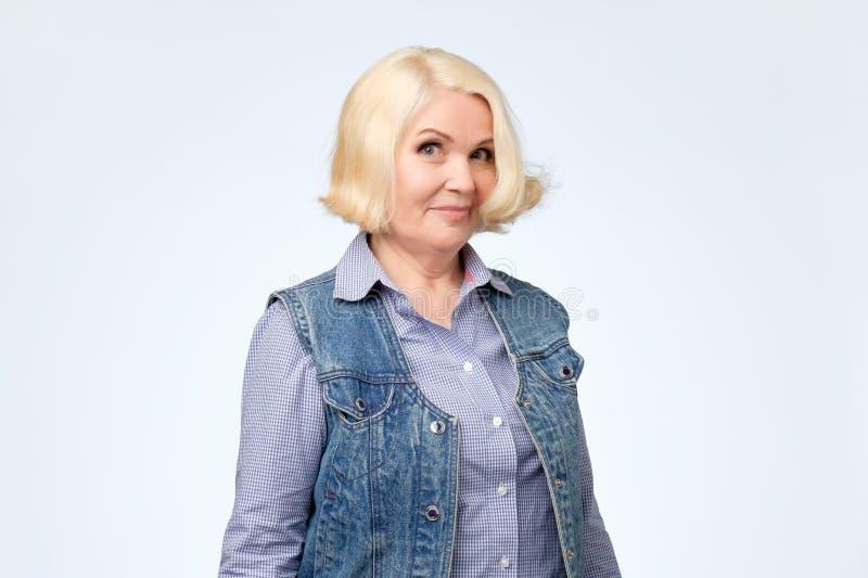 Den höga kvinnan i jeansväst och blå skjorta ler med misstro i hennes ögon royaltyfri fotografi