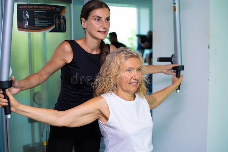 Den höga kvinnan kopplas in på en simulator i idrottshallen med en personlig instruktör dottern hjälper mamman i idrottshallen arkivfoto