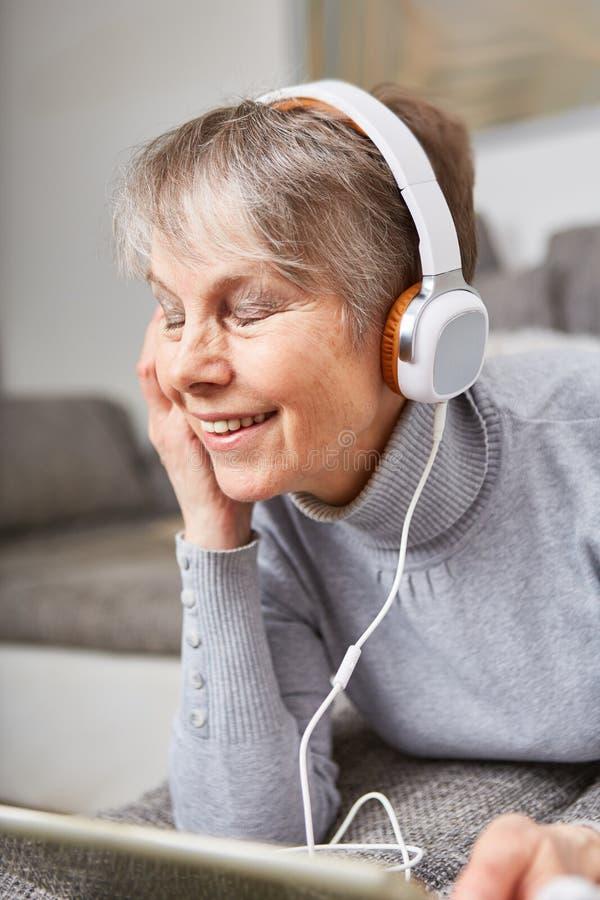 Den höga kvinnan lyssnar till musik med njutning royaltyfri bild