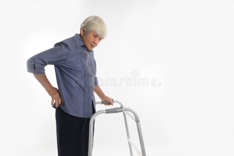 Den höga kvinnan med att gå ramen har att ha en ryggvärk arkivbild