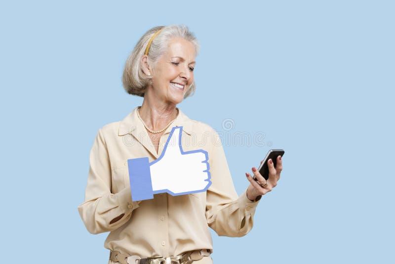 Den höga kvinnan med mobiltelefoninnehavet fejkar som knappen mot blå bakgrund arkivbild