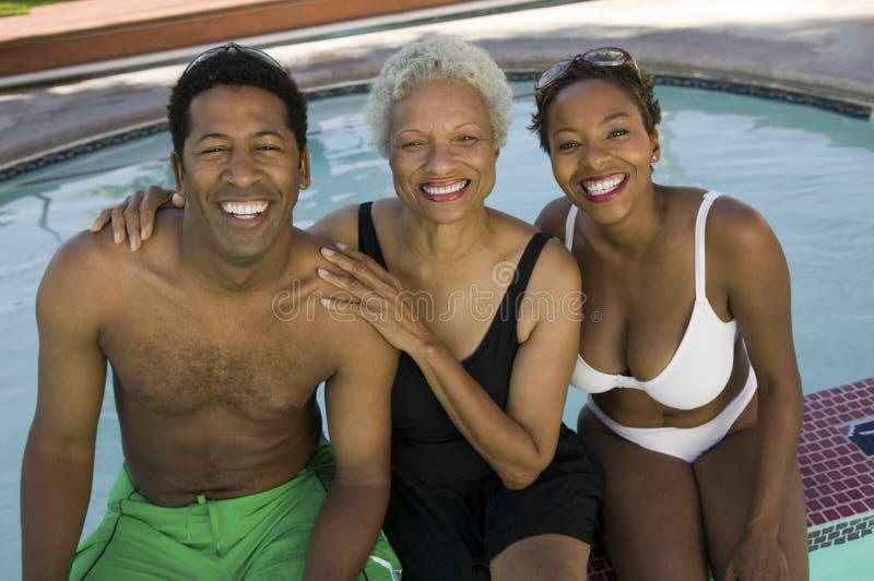 Den höga kvinnan med par på den höjde simbassängen beskådar ståenden. fotografering för bildbyråer