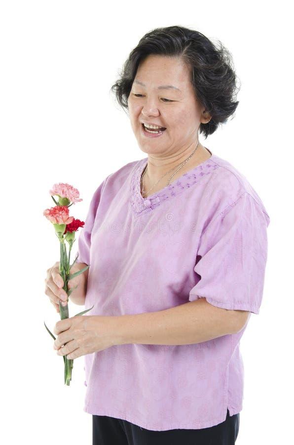 Den höga kvinnan och nejlikan blommar på moderdag royaltyfria foton