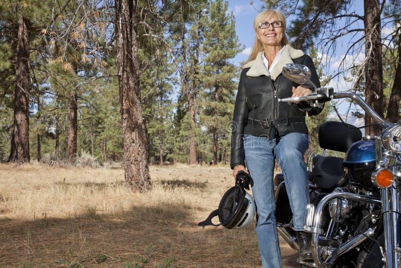 Den höga kvinnan poserar med motorcykeln i skog arkivfoto