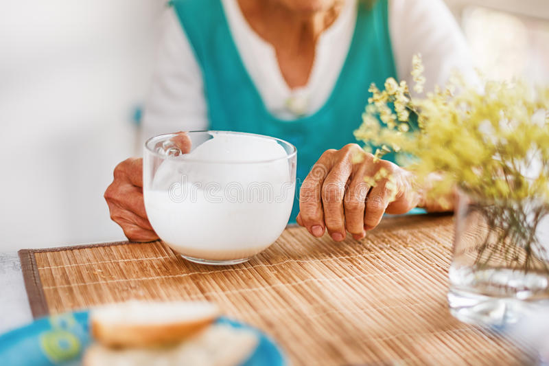 Den höga kvinnan räcker den hållande stora koppen av yoghurt Den gamla kvinnan som rymmer ett exponeringsglas av, mjölkar, hälsov royaltyfri foto